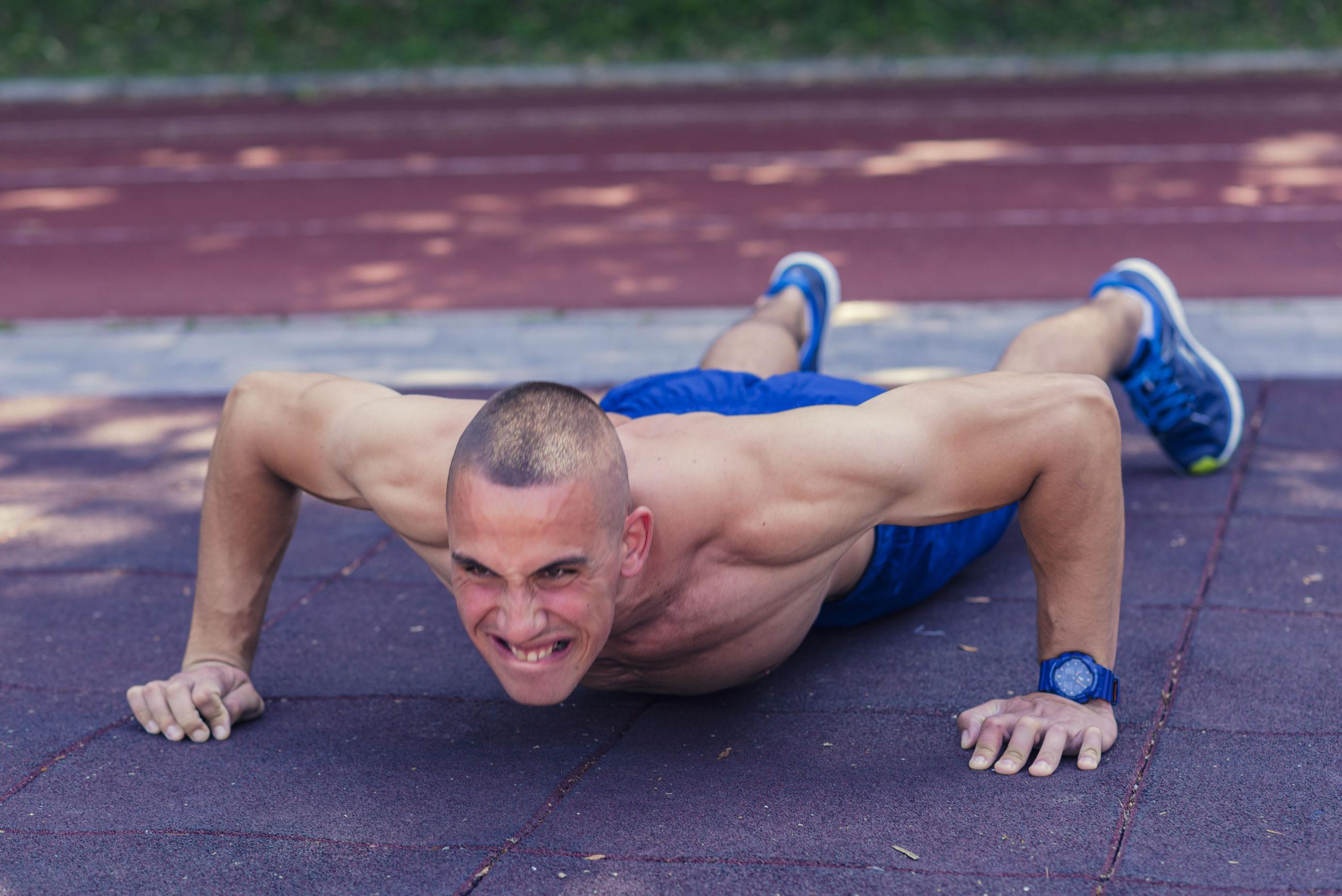 Shirtless muscular man practicing push-ups on street