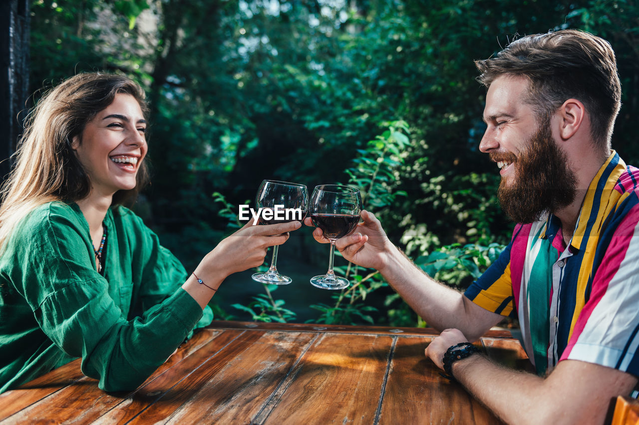 Smiling Young Couple Toasting Wineglasses While Sitting At Table