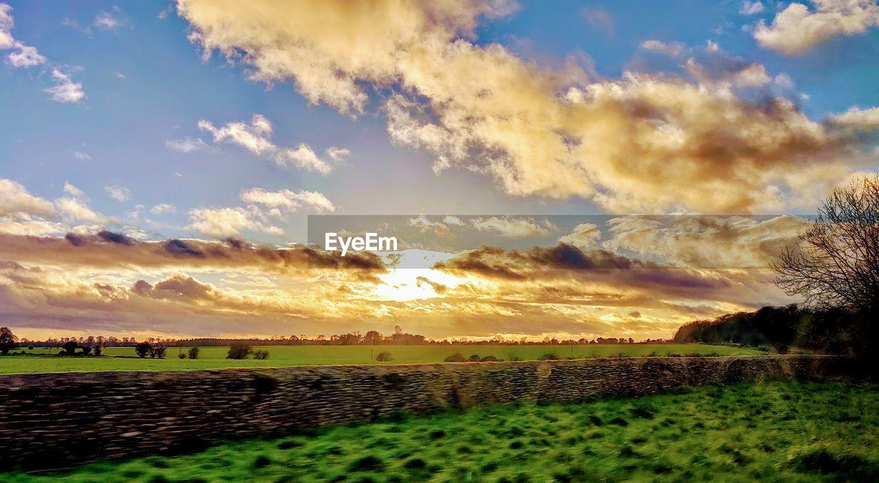 sky, cloud - sky, sunset, scenics - nature, beauty in nature, tranquil scene, nature, tranquility, land, plant, environment, sunlight, field, landscape, idyllic, no people, non-urban scene, outdoors, orange color, rural scene, bright