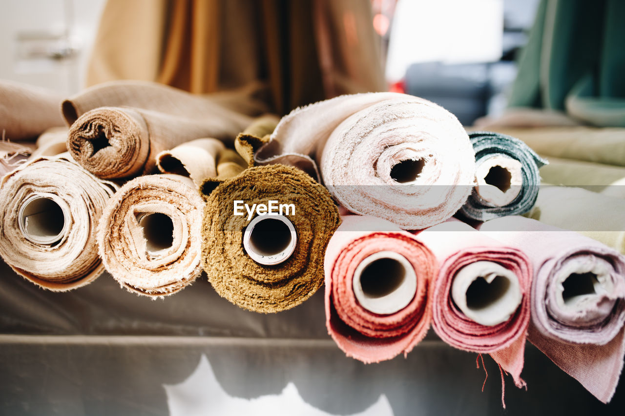 rolled up, choice, variation, focus on foreground, large group of objects, no people, indoors, still life, close-up, for sale, abundance, textile, retail, day, roll, art and craft, group, group of objects, textile industry, collection