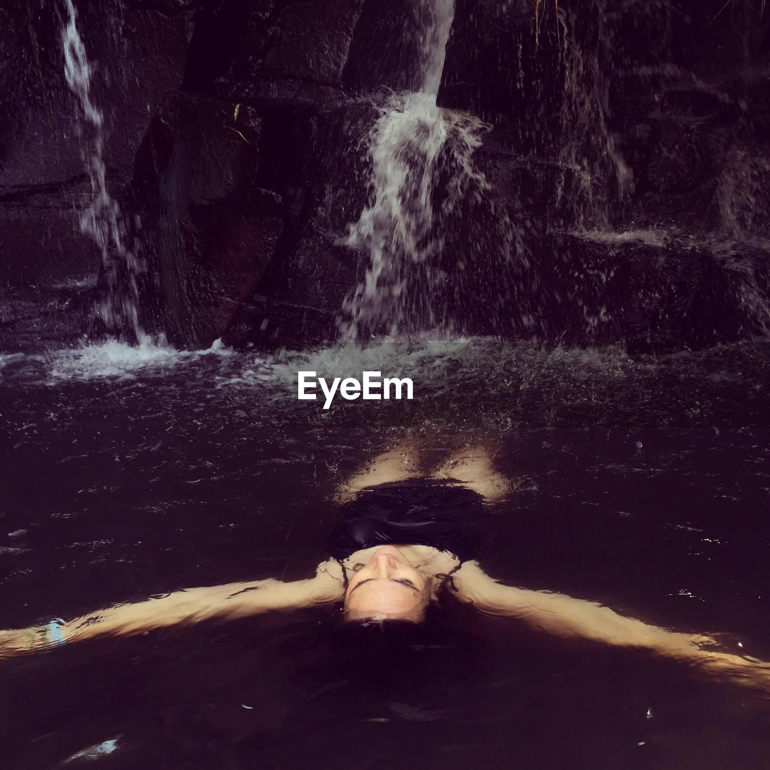 High angle view of woman floating on water at waterfall