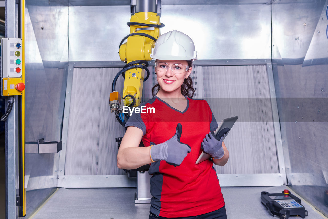 Portrait Of Smiling Technician Gesturing Thumbs Up While Standing Against Machinery In Factory