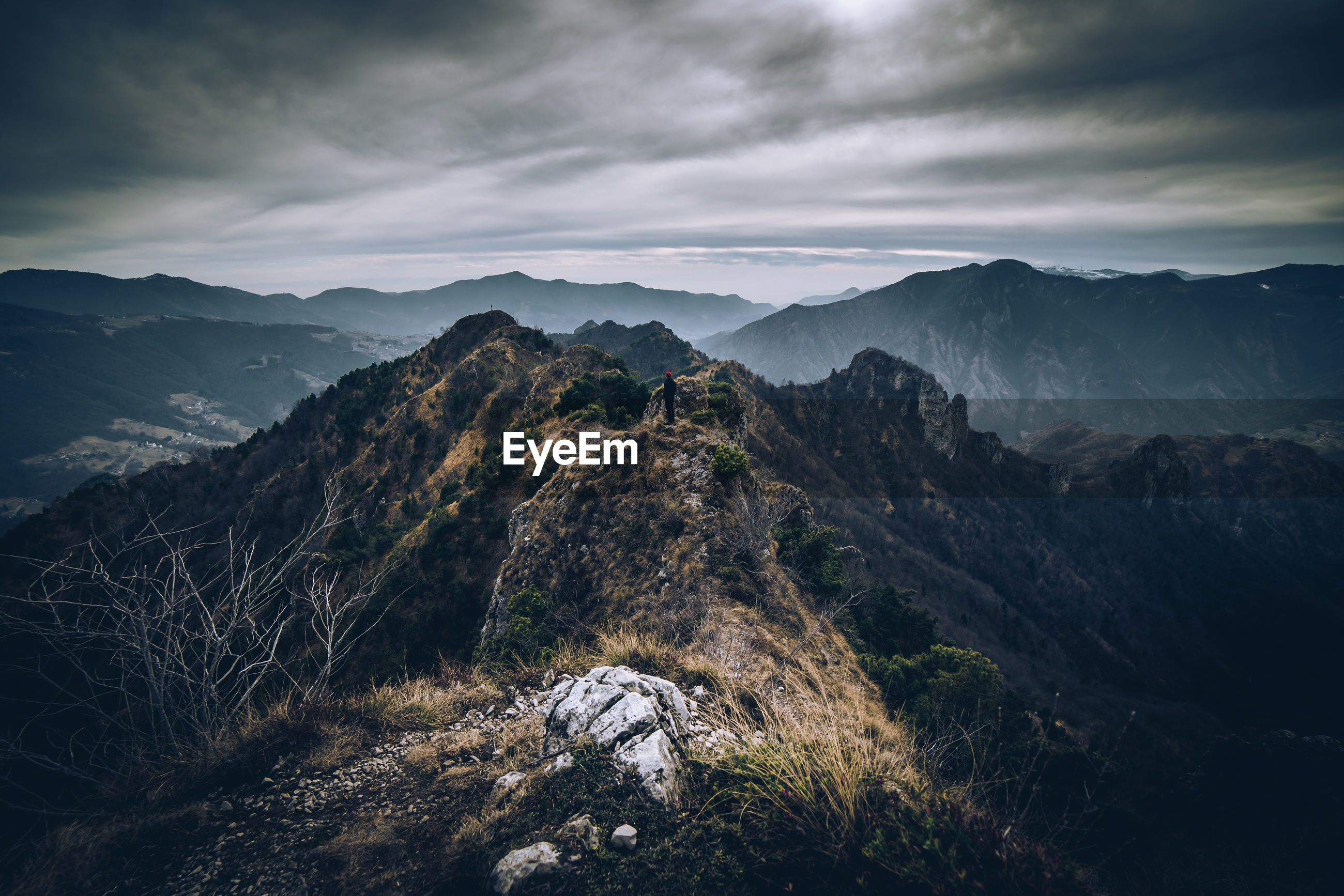 Scenic view of man on mountains against sky