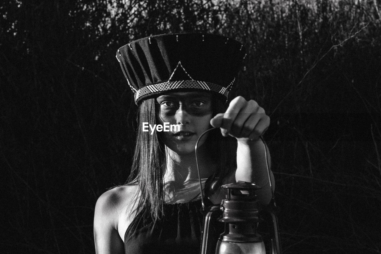 portrait, one person, headshot, front view, young women, young adult, real people, lifestyles, leisure activity, holding, fashion, bottle, tree, long hair, drink, hat, looking at camera, plant, hairstyle, black background