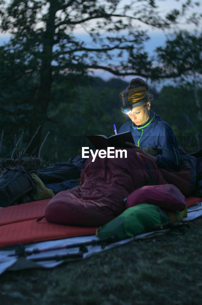 Woman Writing In Book While Sitting On Field
