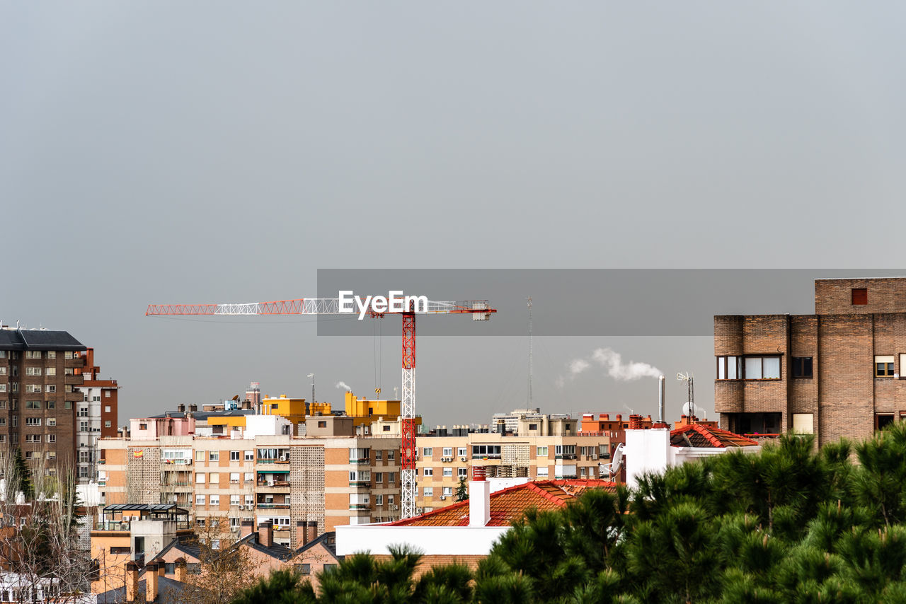 building exterior, architecture, built structure, sky, building, copy space, nature, city, no people, residential district, clear sky, plant, tree, outdoors, day, machinery, construction industry, crane - construction machinery, industry, apartment