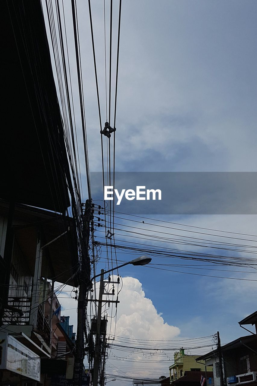 LOW ANGLE VIEW OF ELECTRICITY PYLON AMIDST BUILDINGS IN CITY AGAINST SKY