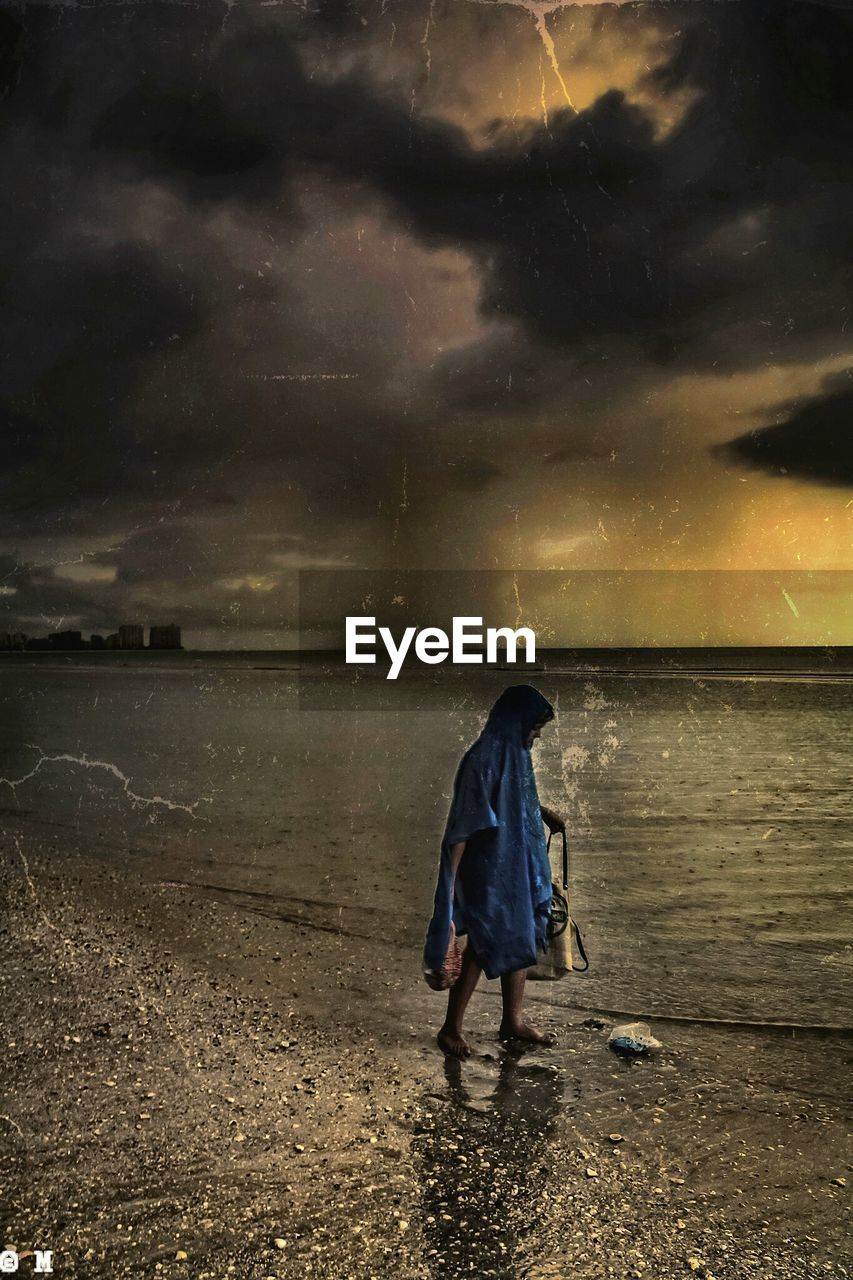 water, full length, sky, cloud - sky, sunset, weather, rear view, sea, nature, real people, outdoors, one person, tranquility, standing, beach, horizon over water, scenics, beauty in nature, childhood, storm cloud, boys, day, people