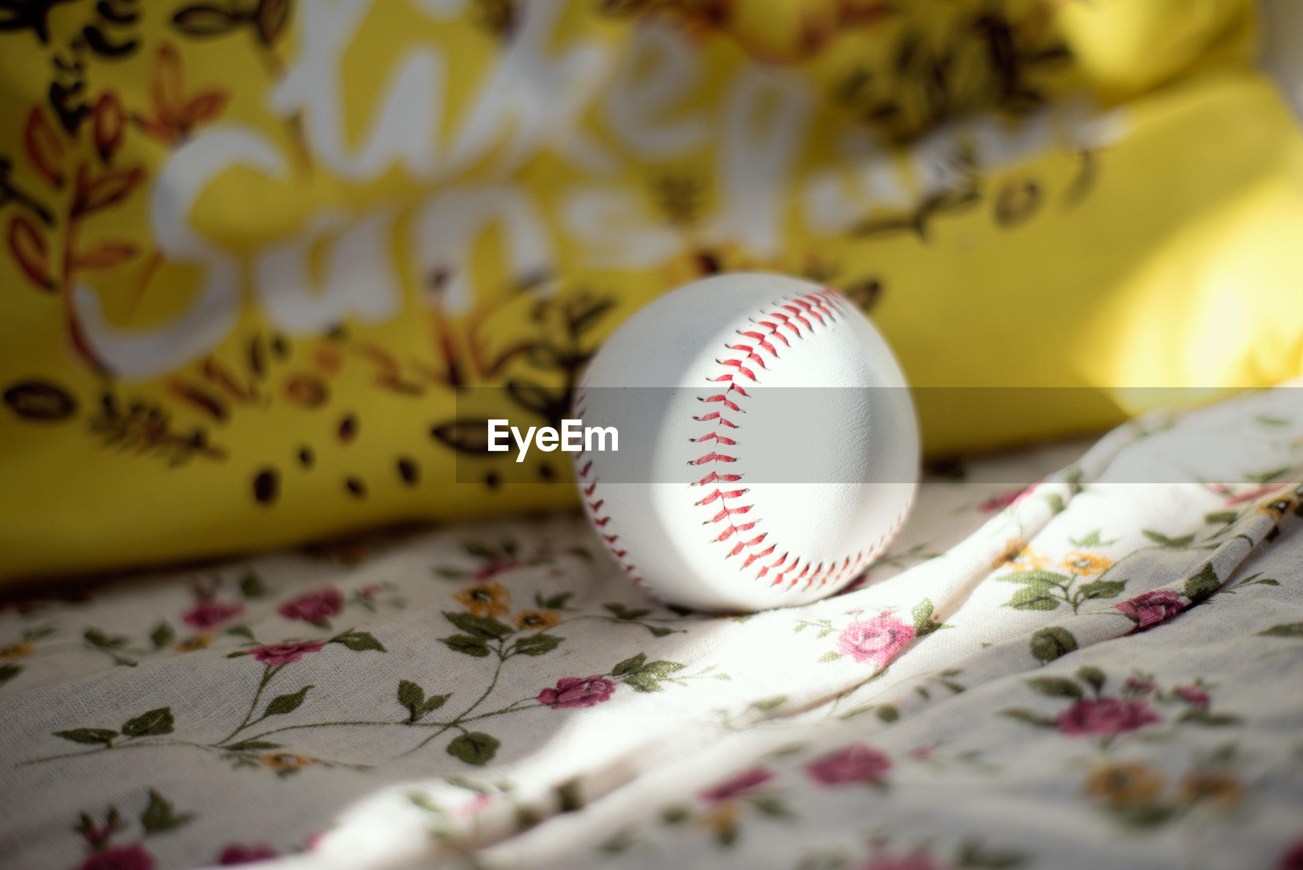 baseball, baseball - ball, sports, selective focus, indoors, yellow, no people, ball, pink, pattern, close-up, baseball glove, team sport, furniture, white
