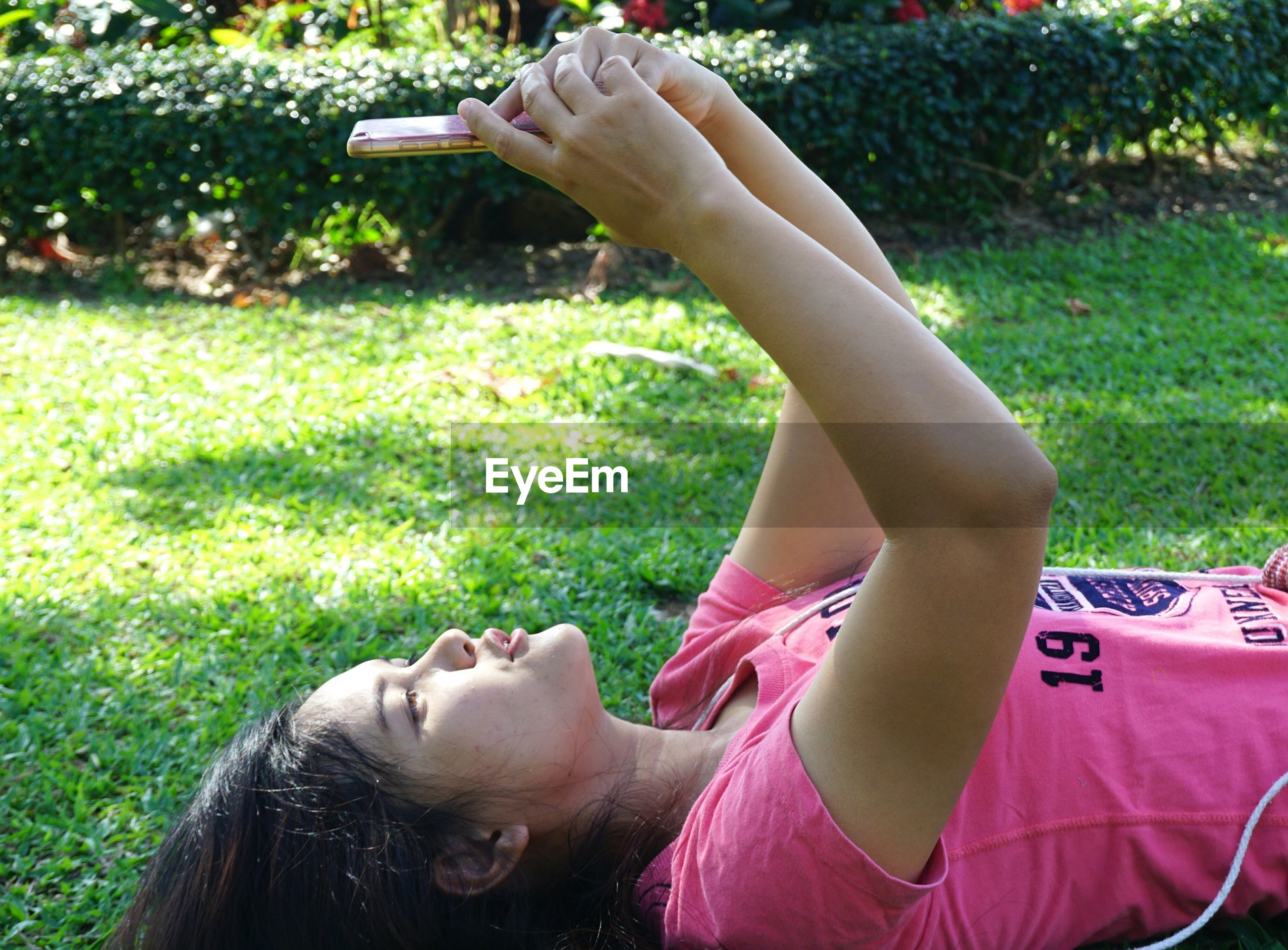 Side view of woman using mobile phone while lying on grass
