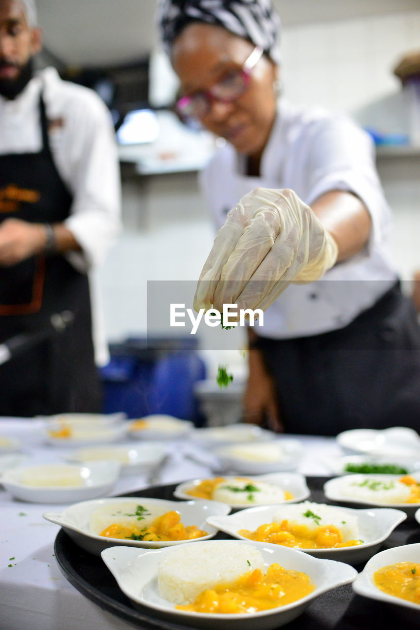 Mature woman garnishing food while standing in commercial kitchen