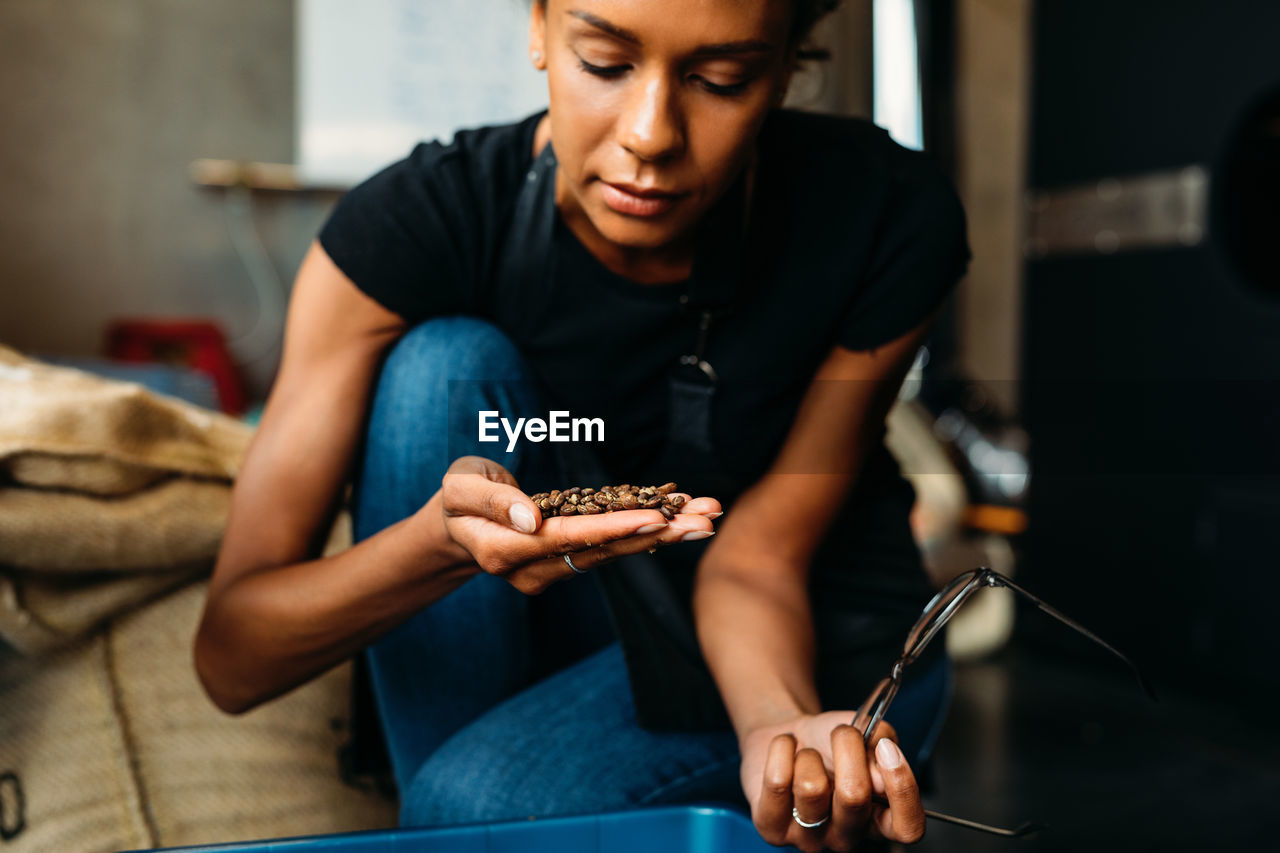 Young woman looking coffee beans in cafe