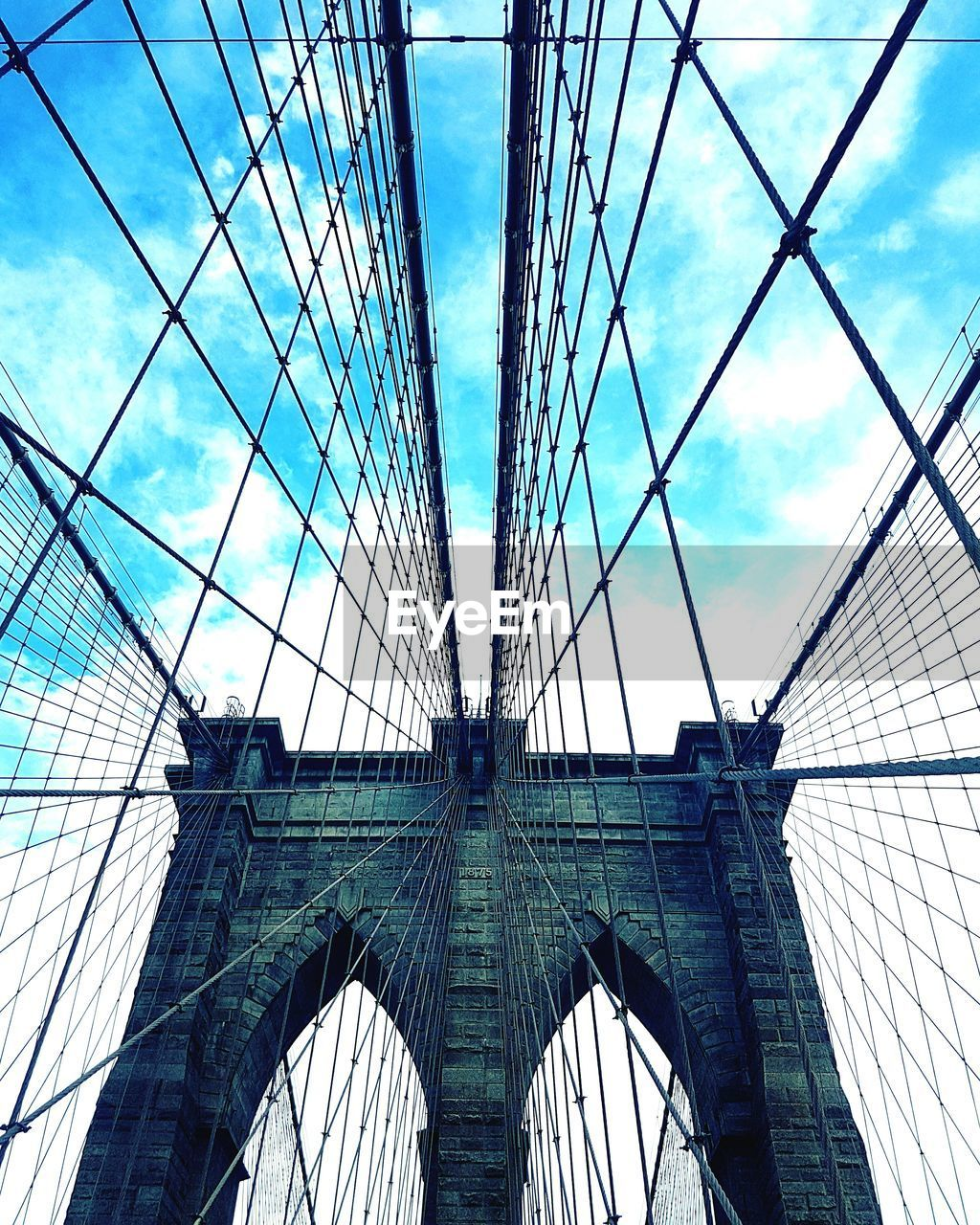 bridge - man made structure, architecture, connection, built structure, engineering, low angle view, suspension bridge, sky, modern, transportation, day, bridge, no people, skyscraper, city, outdoors, building exterior