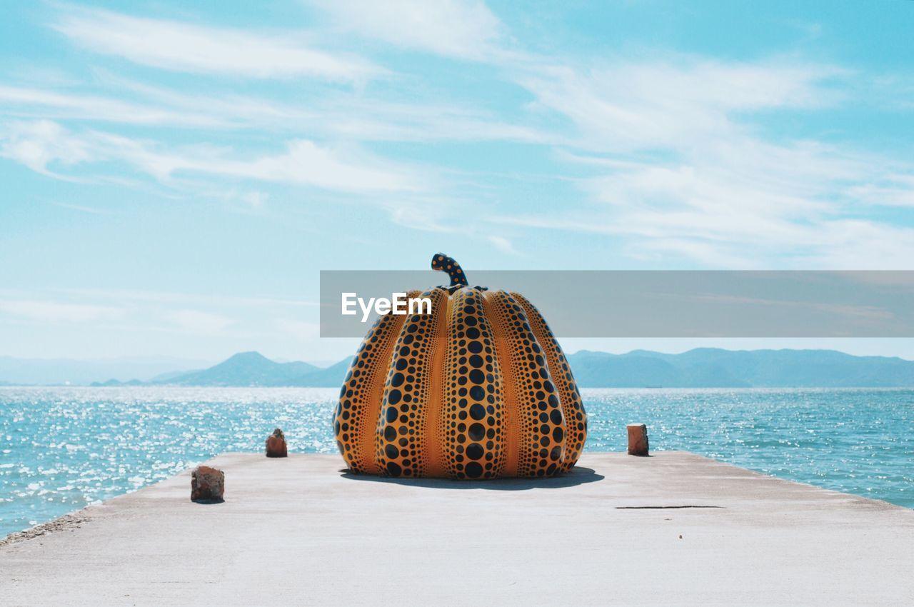 Pumpkin Decoration Of Pier At Beach Against Sky