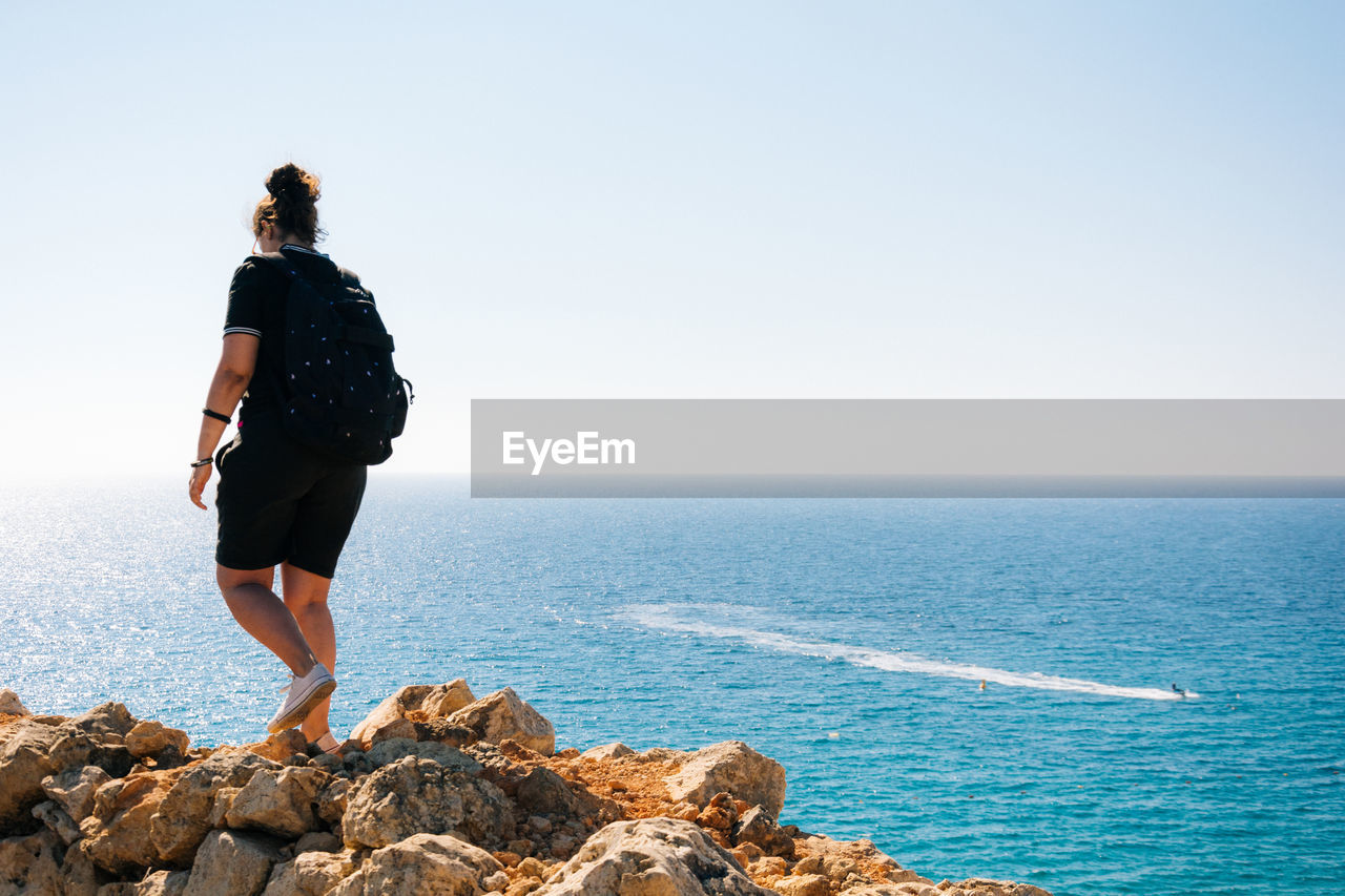 Rear view full length of woman on rocks against sea