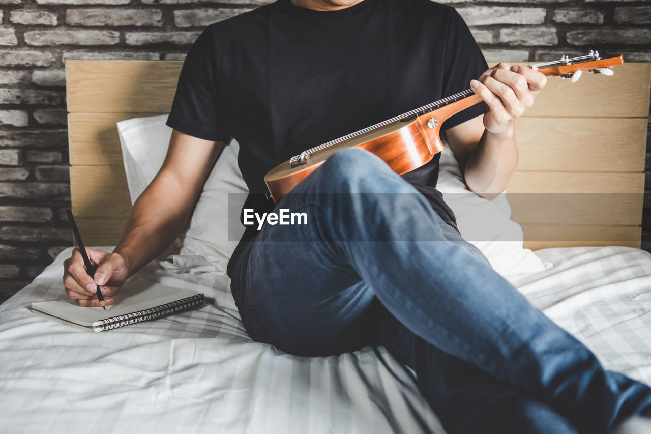 Midsection Of Man Holding Musical Instrument While Sitting On Bed At Home