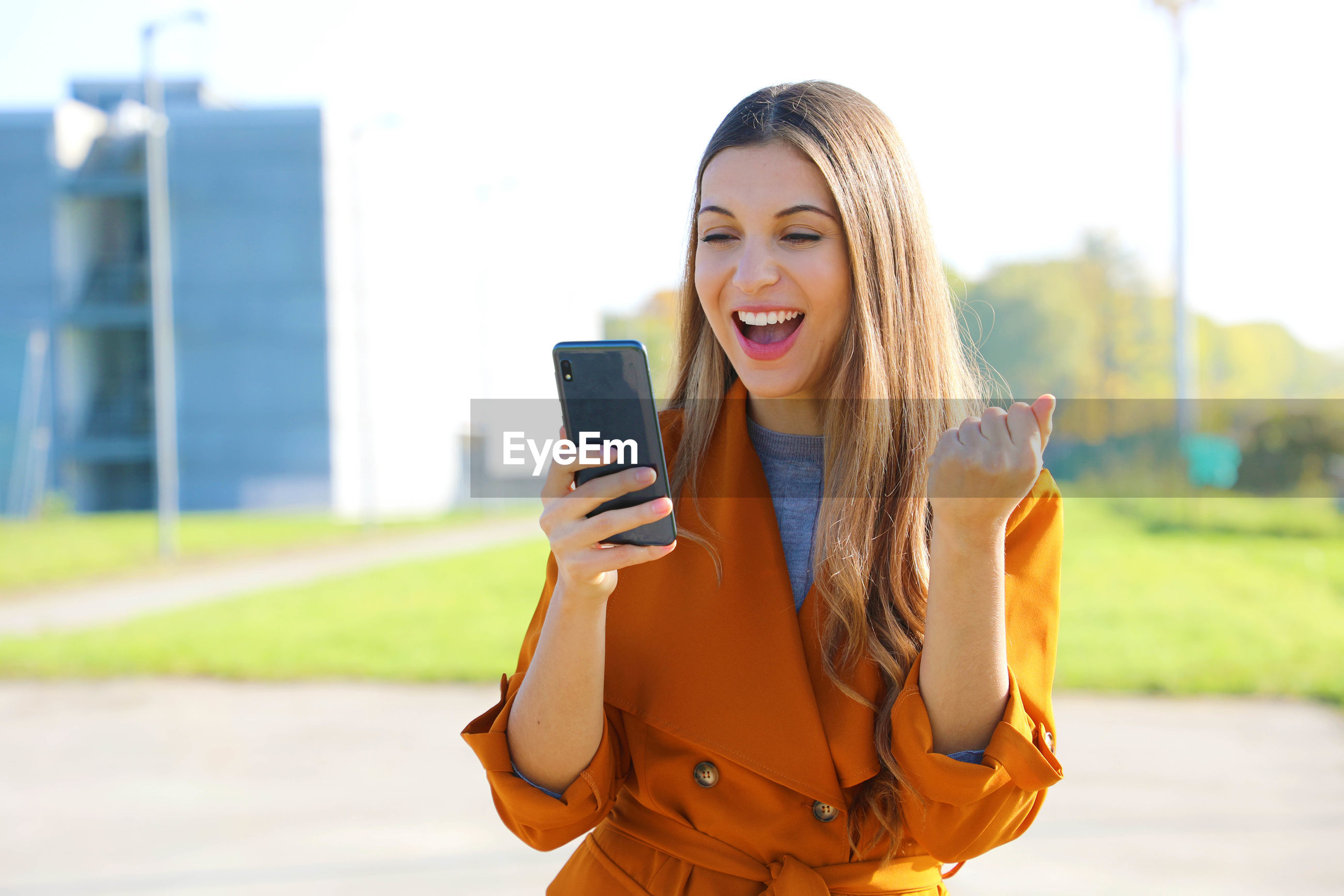 Smiling young woman gesturing while using smart phone