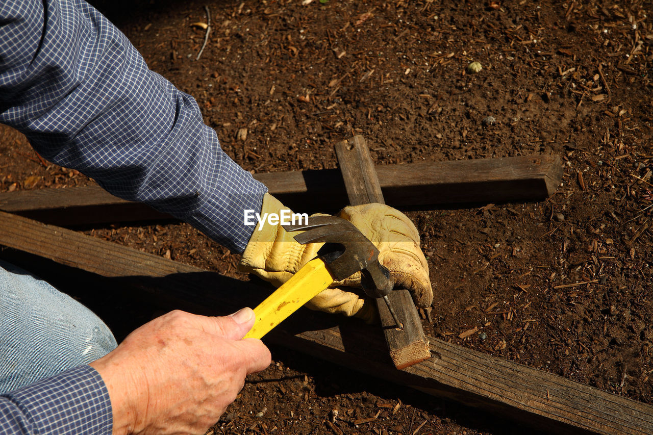 Close-Up Of Hammering Nail On Wood