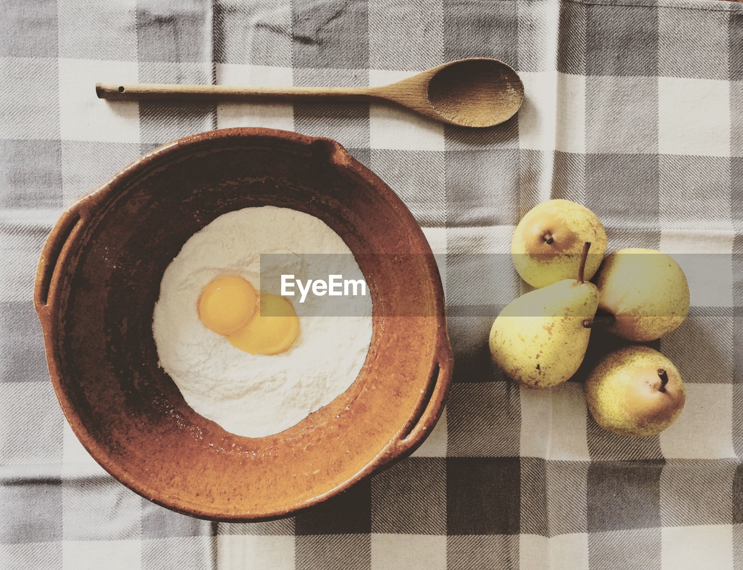 High angle view of egg and flour in container by pears on table