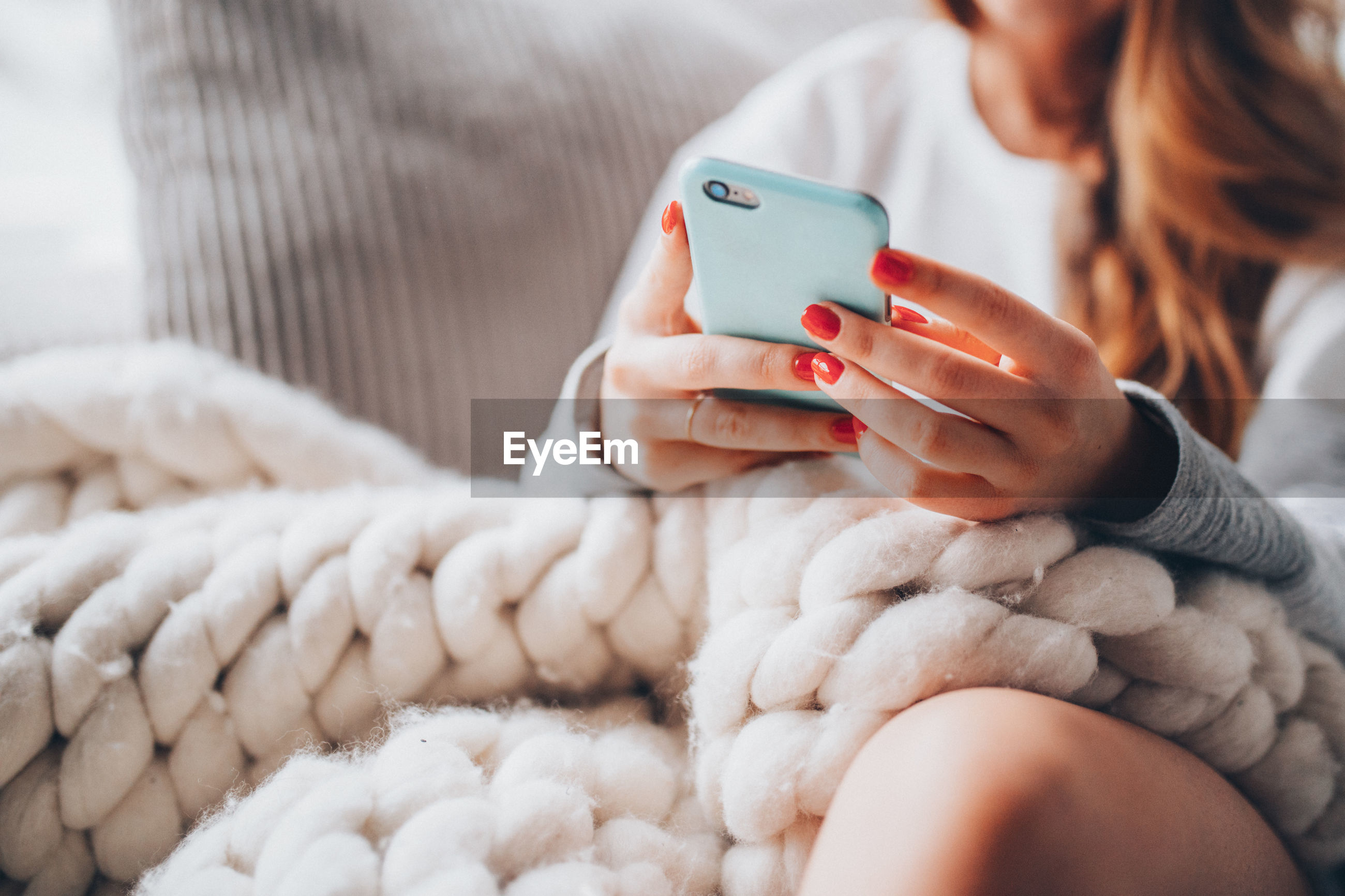 Midsection of woman using mobile phone while sitting on bed at home