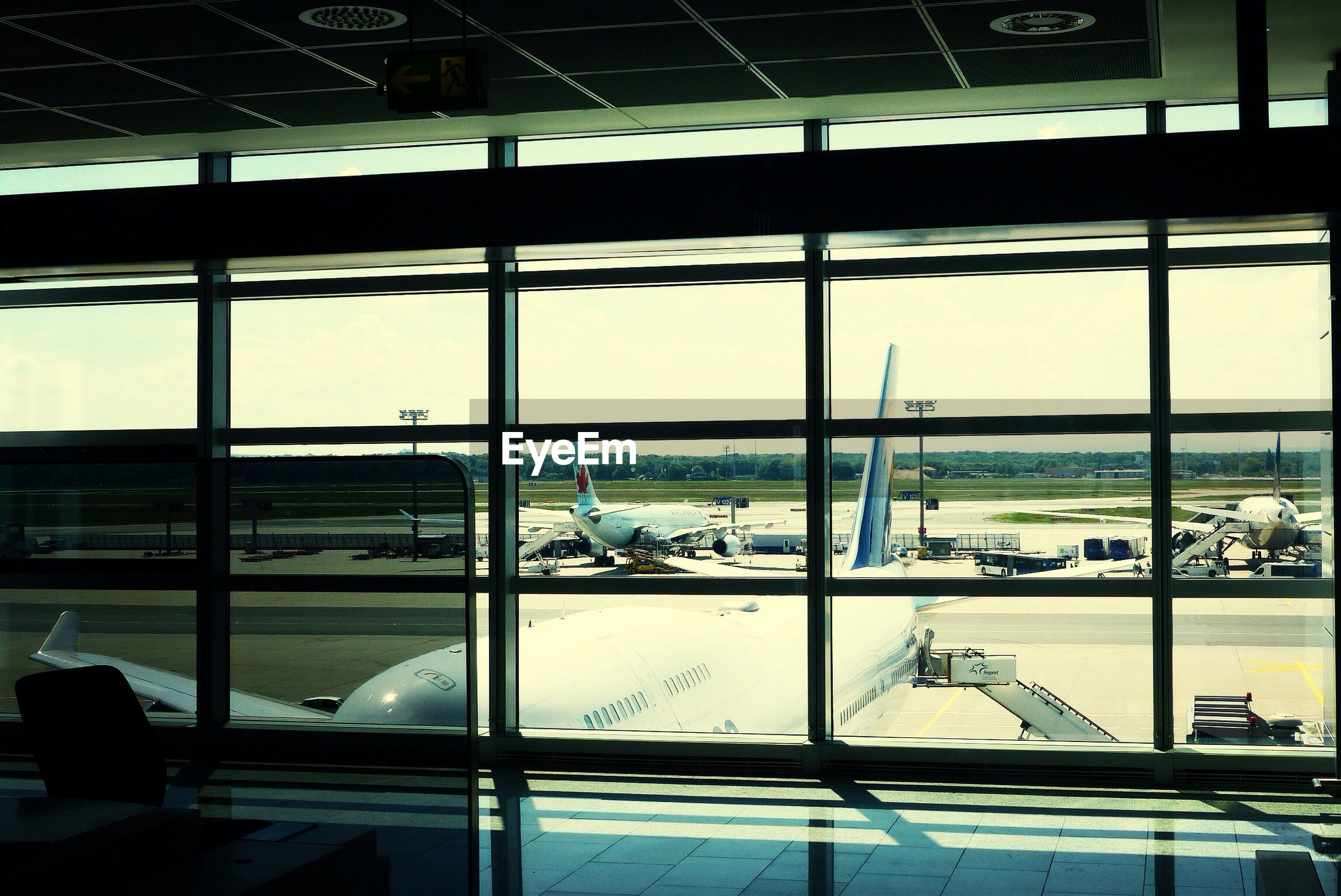 window, glass - material, indoors, transparent, built structure, architecture, glass, sky, airport, city, day, chair, restaurant, looking through window, table, reflection, modern, men, building exterior