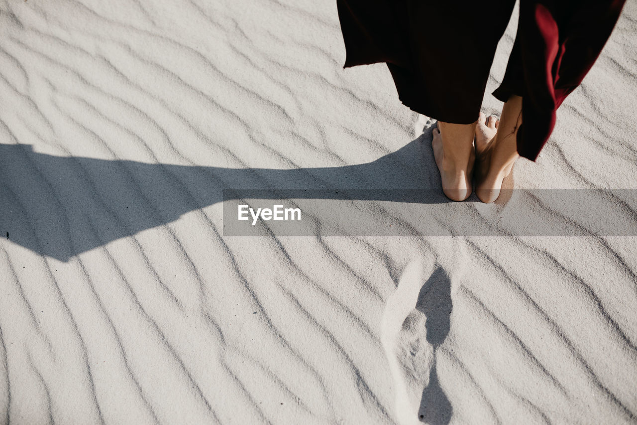 Low Section Of Woman Standing On Sand At Desert