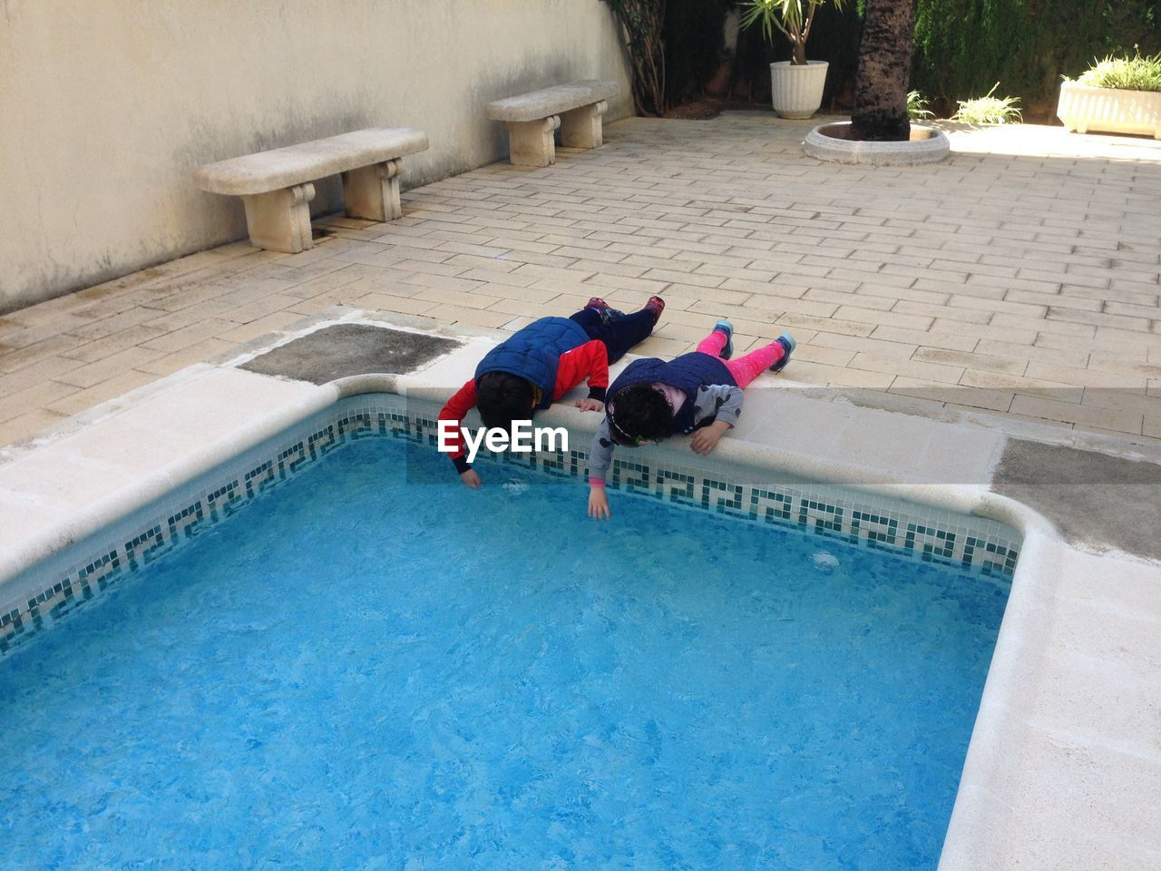 High angle view of children lying down by swimming pool