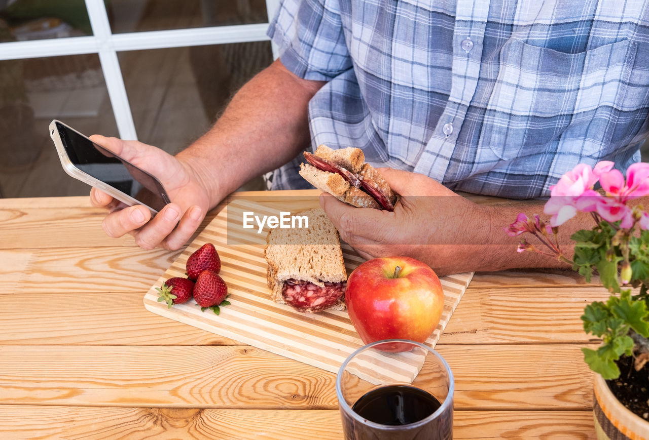 food and drink, food, one person, freshness, human hand, fruit, table, holding, healthy eating, technology, wellbeing, real people, wireless technology, communication, lifestyles, midsection, hand, indoors, human body part, casual clothing, glass