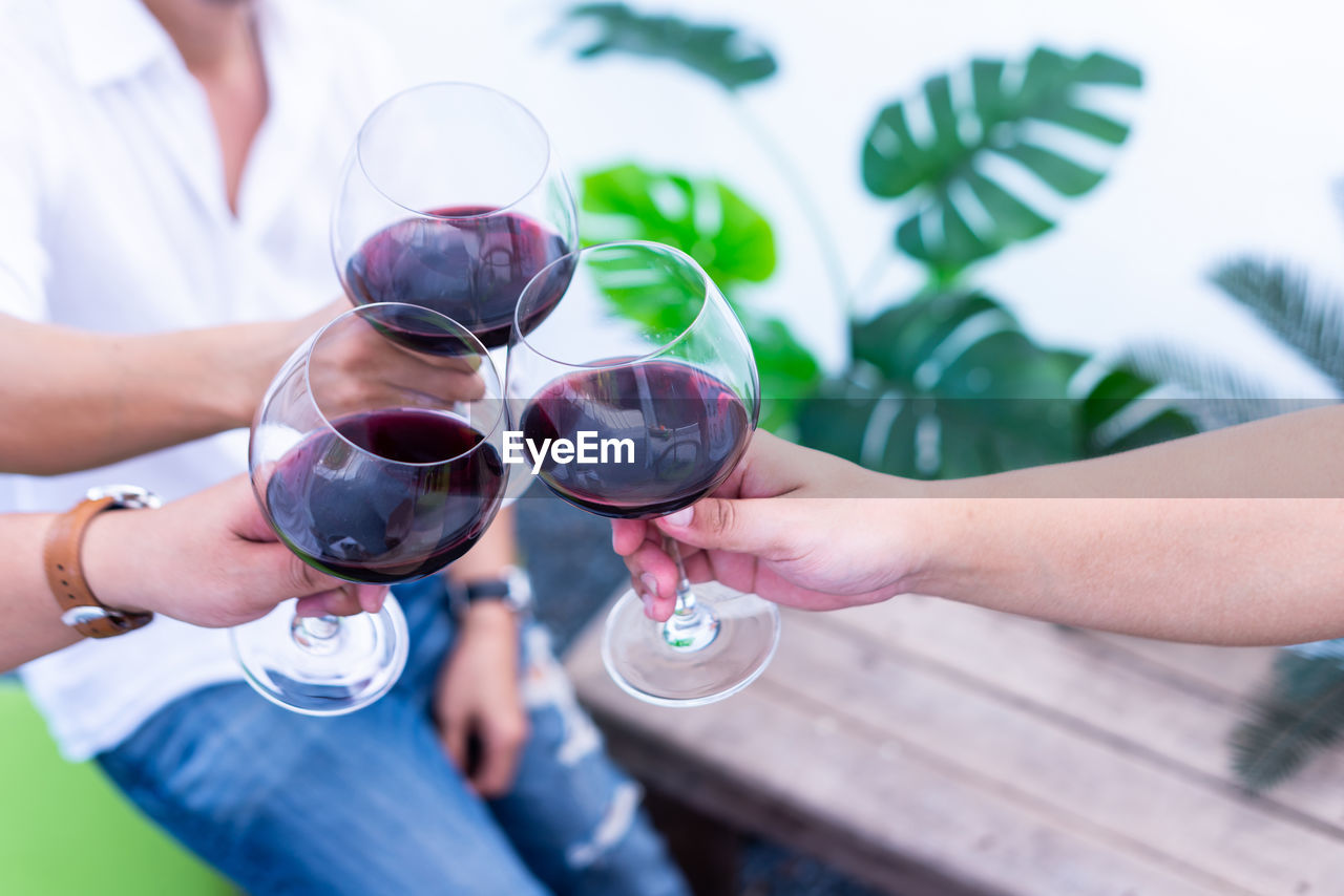 drink, alcohol, glass, hand, real people, wine, holding, refreshment, human hand, celebratory toast, wineglass, food and drink, celebration, human body part, friendship, men, women, lifestyles, togetherness, group of people, red wine
