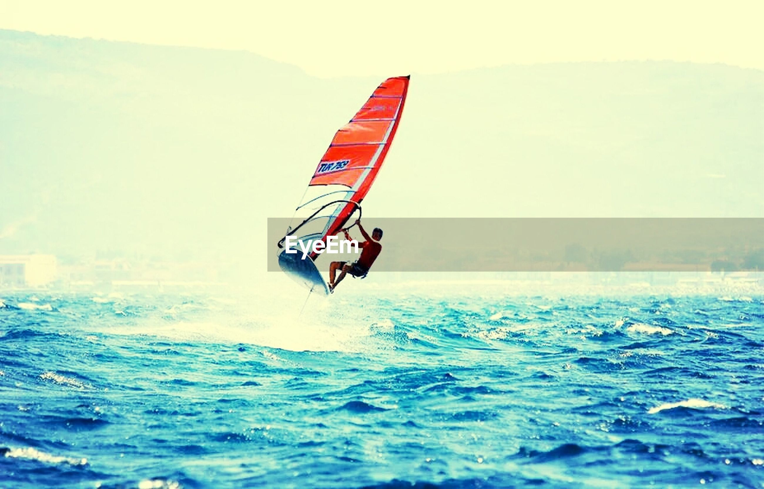 sea, waterfront, water, transportation, nautical vessel, mode of transport, flying, scenics, boat, sailing, travel, sky, mid-air, nature, beauty in nature, horizon over water, extreme sports, tranquility, adventure, flag