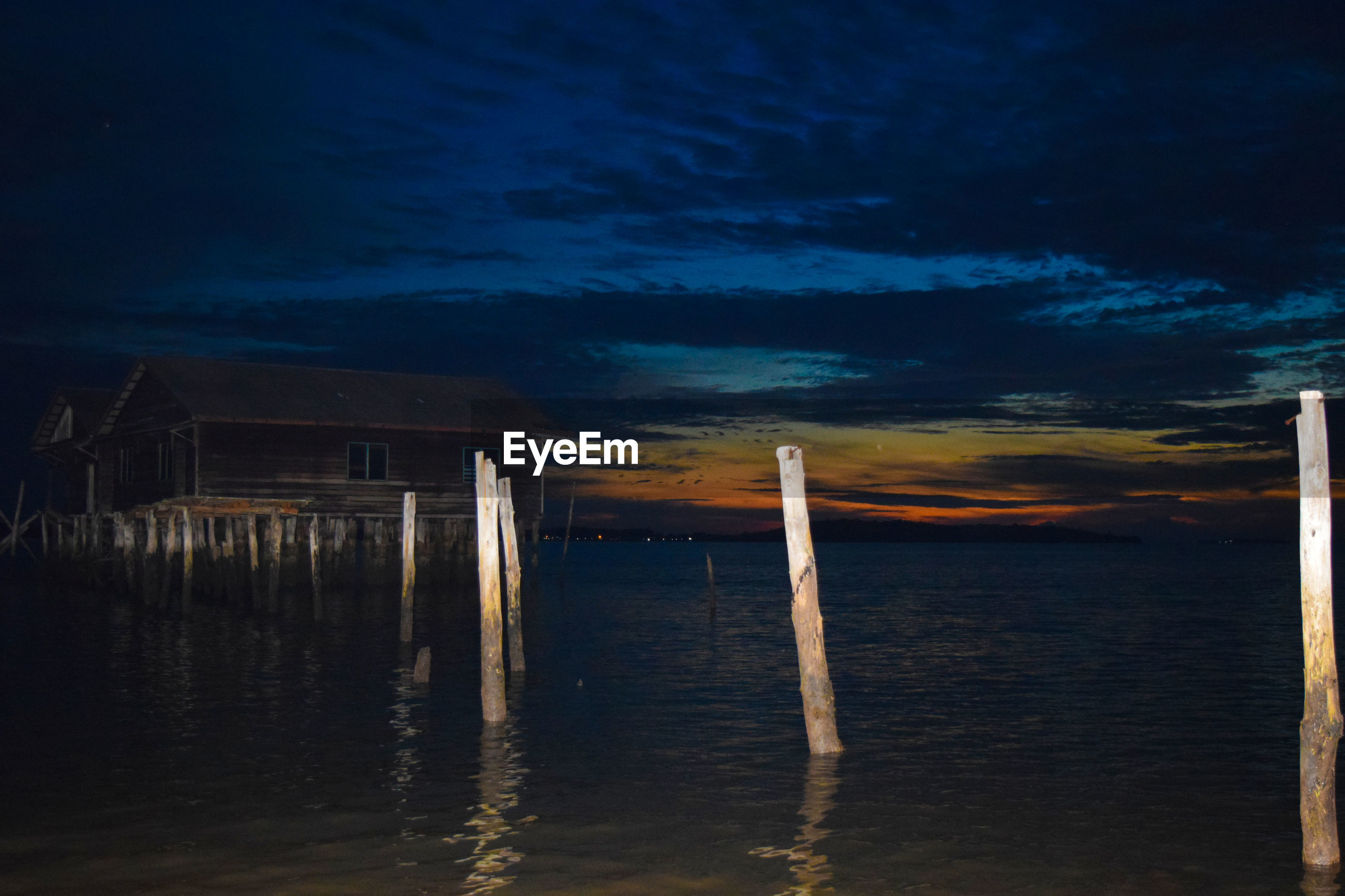 WOODEN POSTS IN SEA AT NIGHT