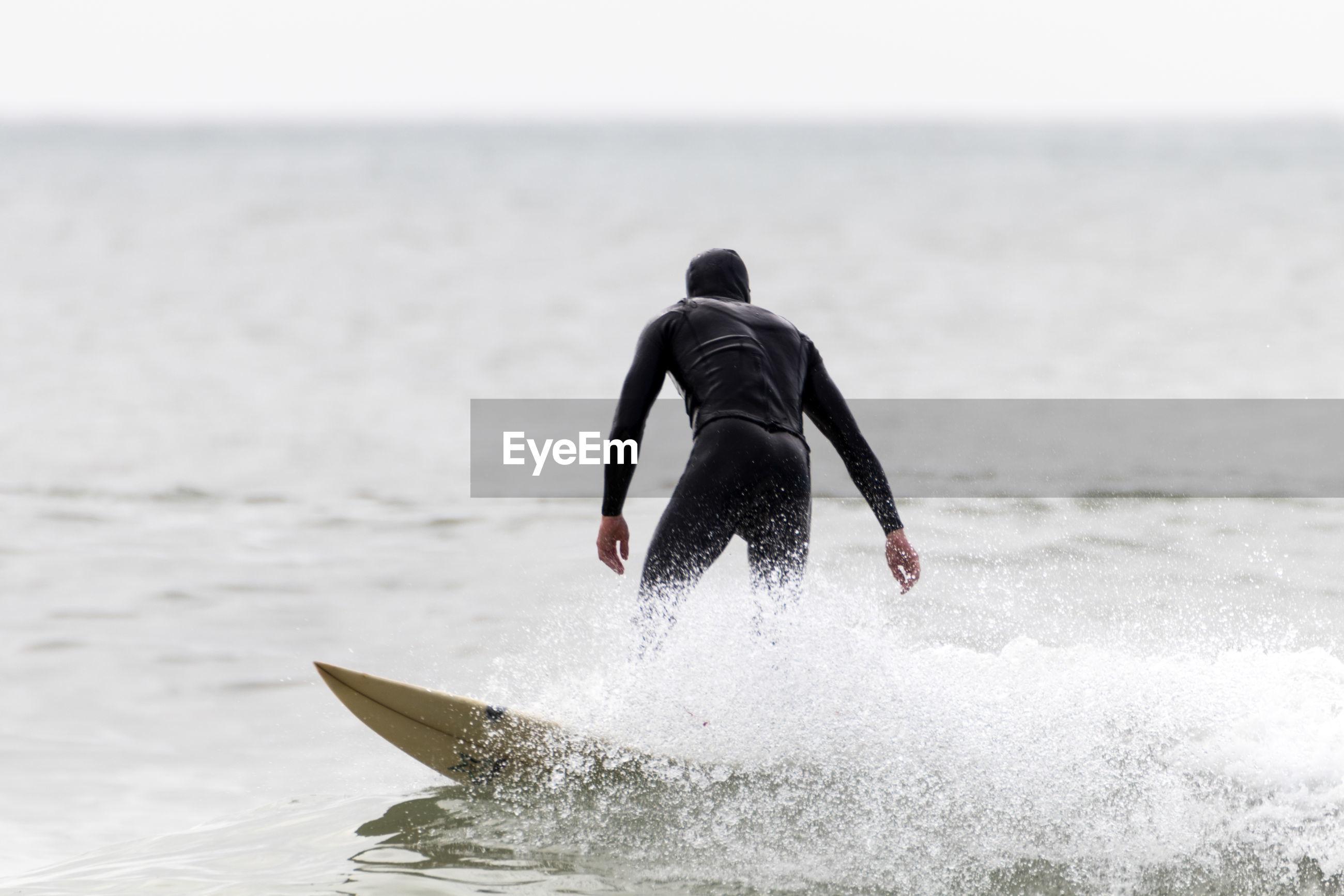 Rear view of man surfboarding in sea against sky