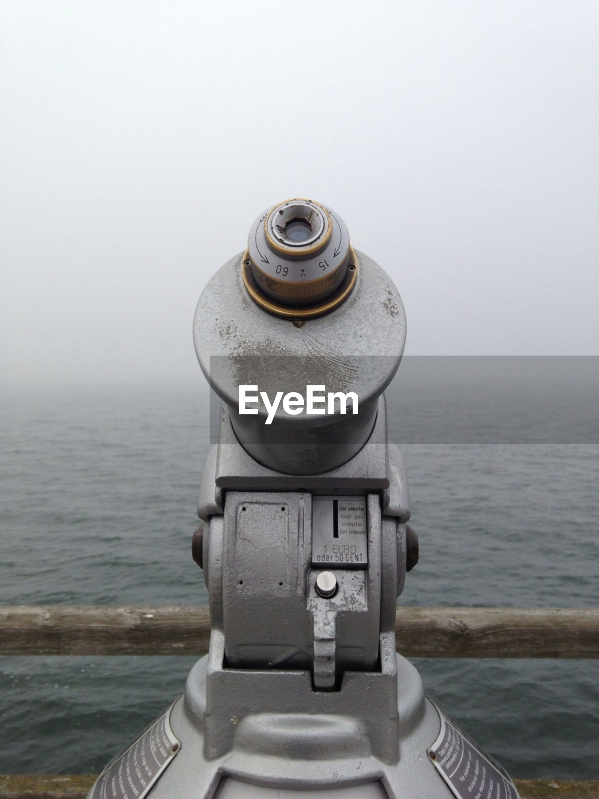 Coin-operated binoculars in front of sea against sky during foggy weather