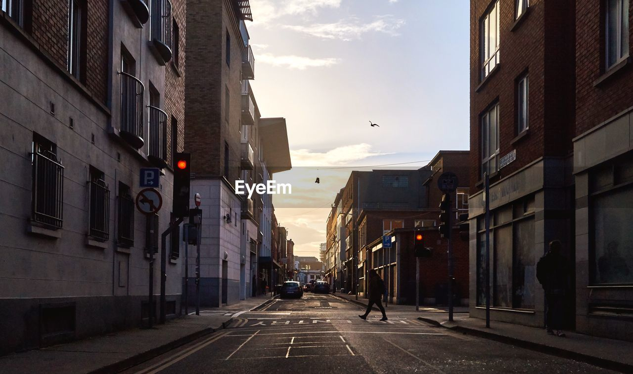 building exterior, architecture, city, built structure, street, building, the way forward, direction, road, sky, sign, transportation, incidental people, residential district, nature, symbol, city street, outdoors, sunset, cloud - sky