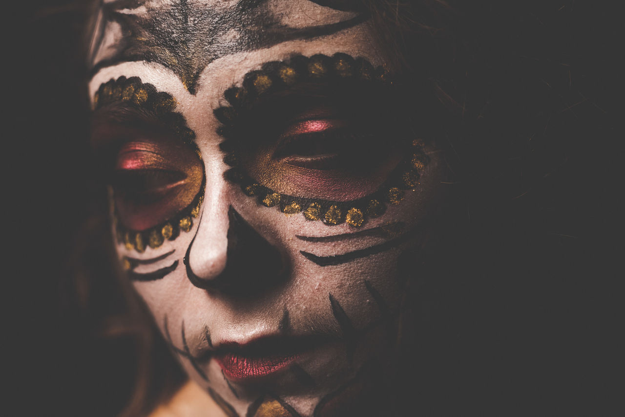 Close-Up Of Thoughtful Model With Face Paint Against Black Background