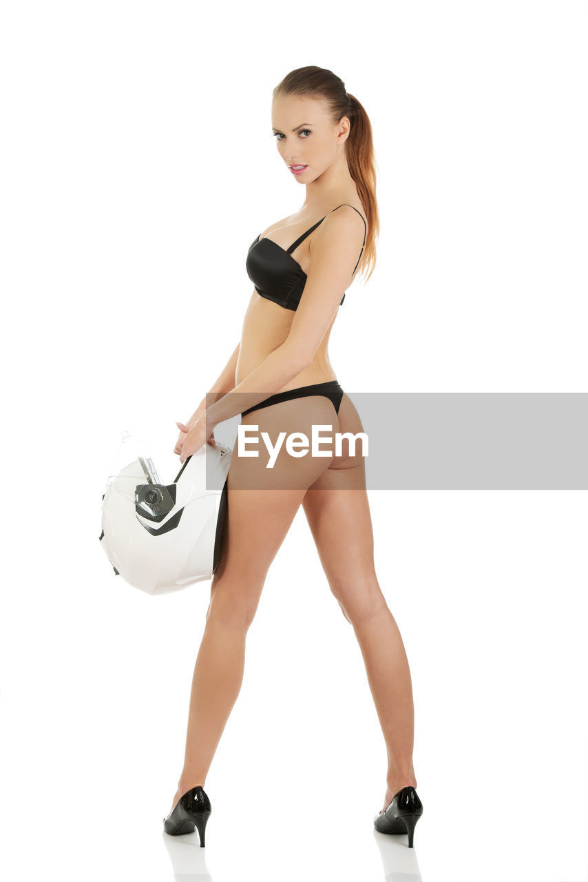 Portrait of woman in lingerie holding helmet while standing against white background