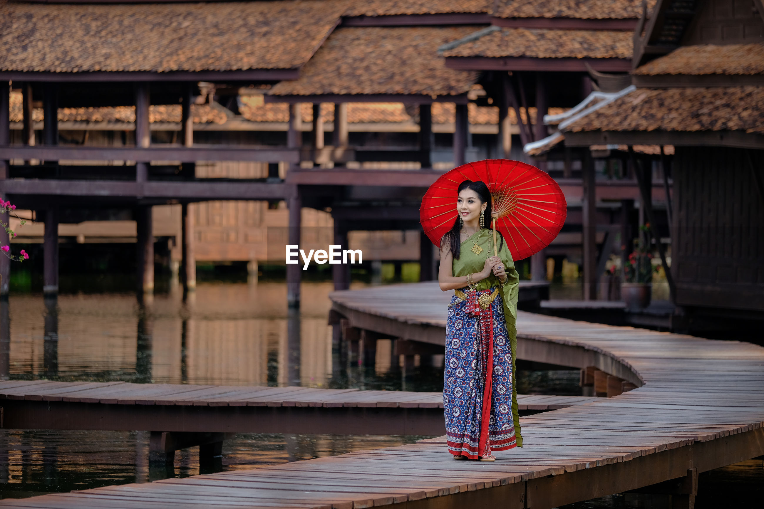 Smiling young woman standing with umbrella on pier against stilt houses