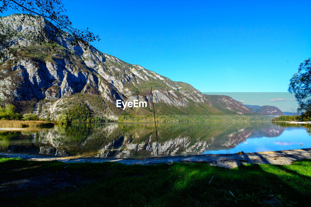 water, sky, mountain, blue, beauty in nature, scenics - nature, lake, nature, tranquil scene, tranquility, clear sky, reflection, no people, mountain range, plant, non-urban scene, rock, day, idyllic, outdoors, formation