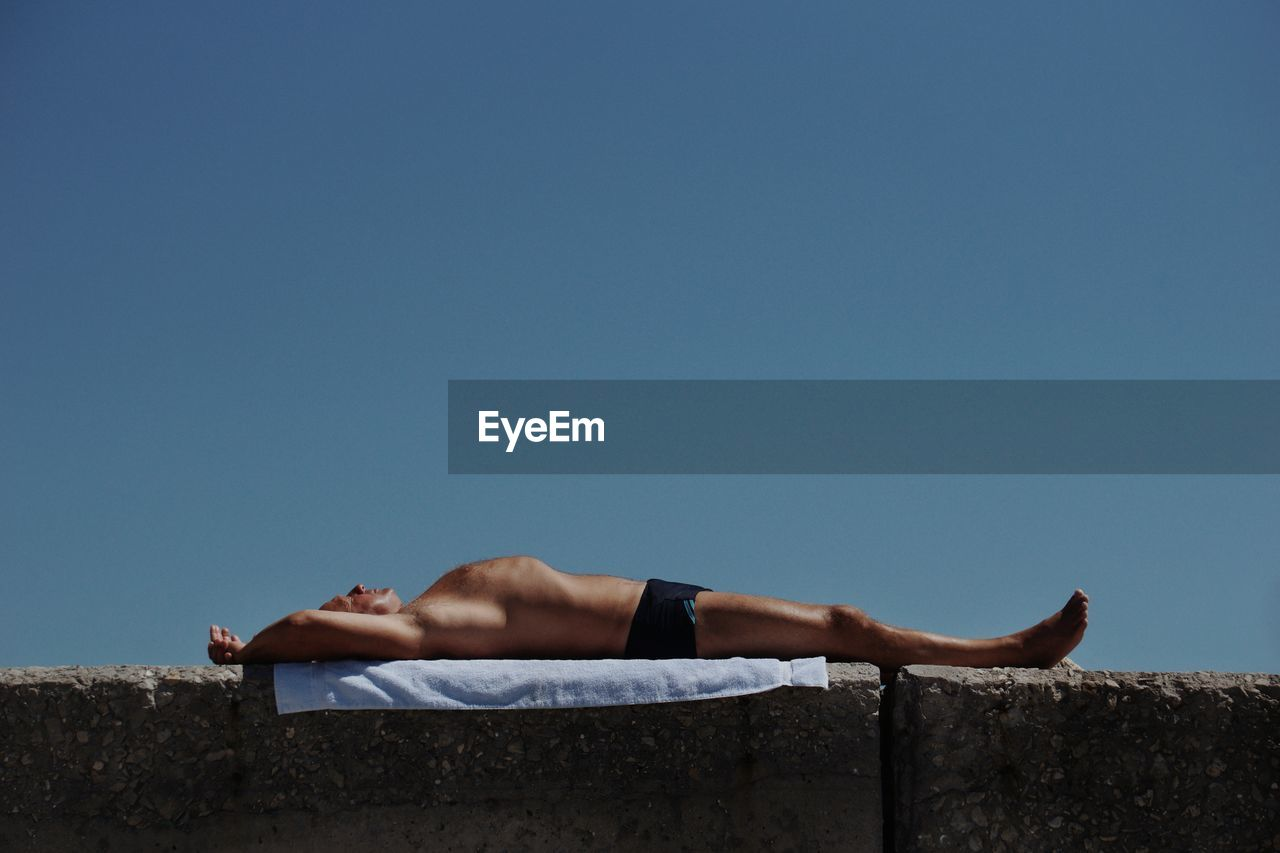 Shirtless man relaxing on retaining wall against clear blue sky