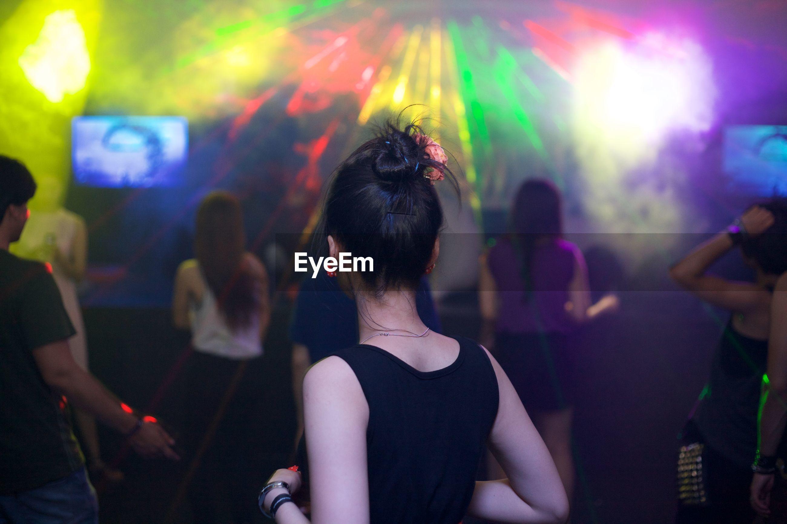 Rear view of people enjoying at nightclub
