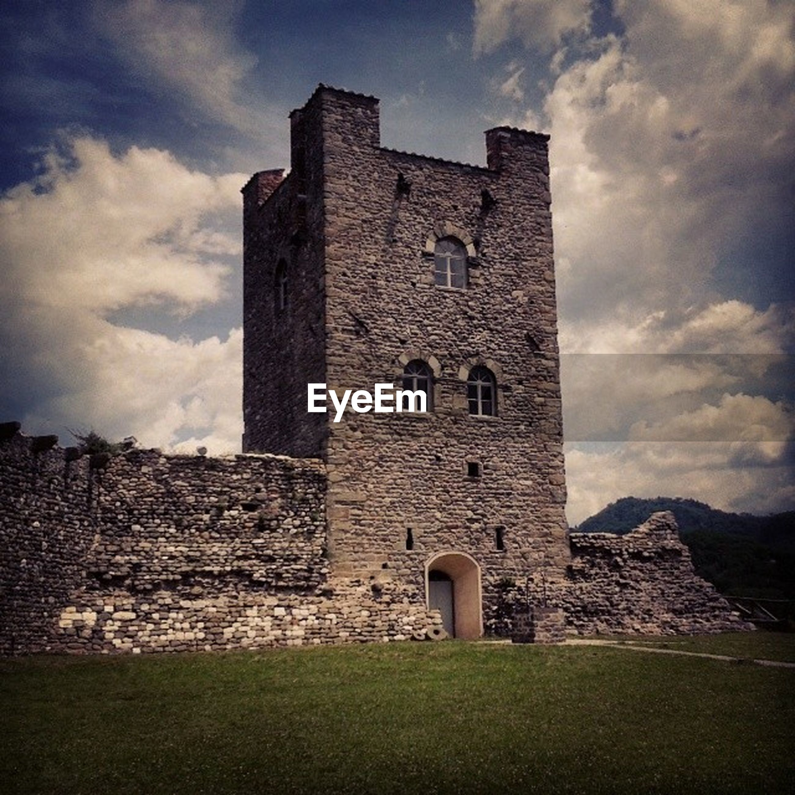 architecture, built structure, building exterior, sky, history, cloud - sky, stone wall, low angle view, grass, the past, old, old ruin, castle, tower, cloud, cloudy, day, outdoors, fort, no people