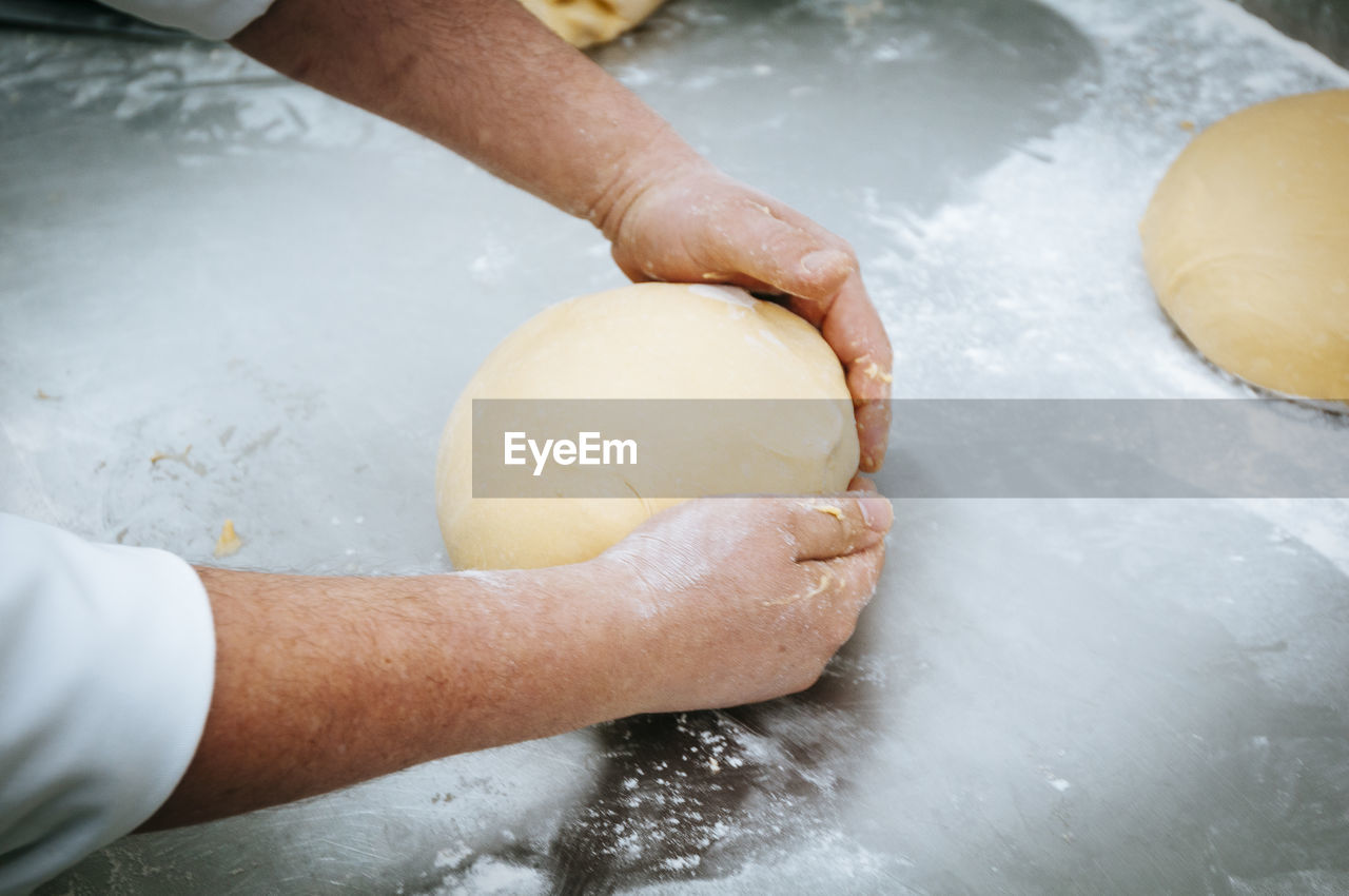 Cropped Hands Kneading Dough On Kitchen Counter