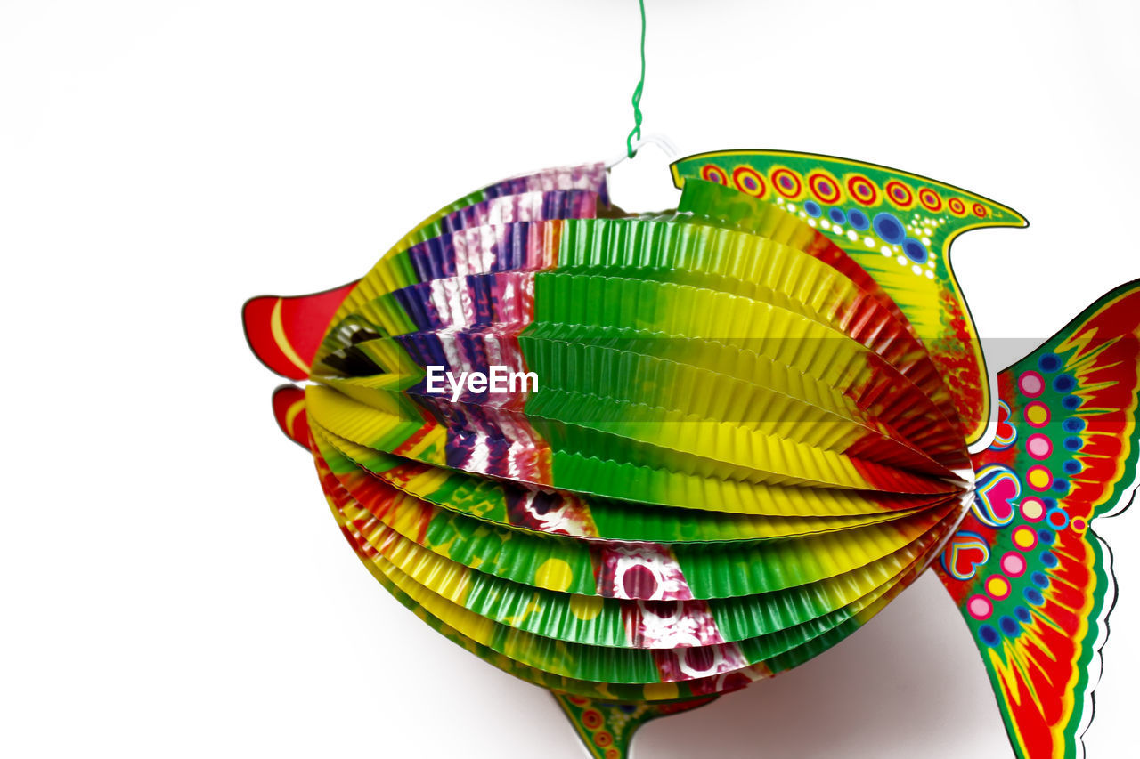 Close-up of colorful paper fish hanging against white background