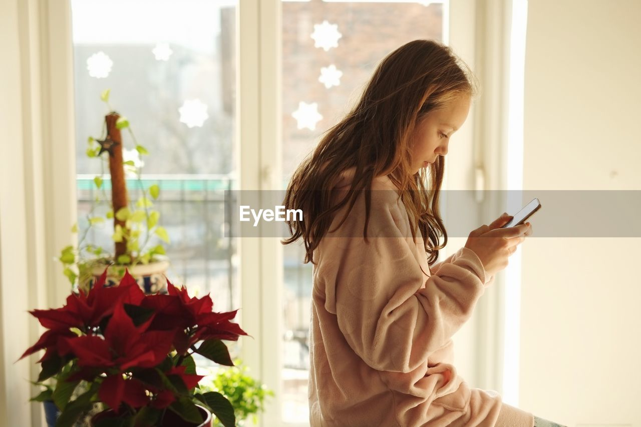 Side View Of Girl Using Mobile Phone By Window