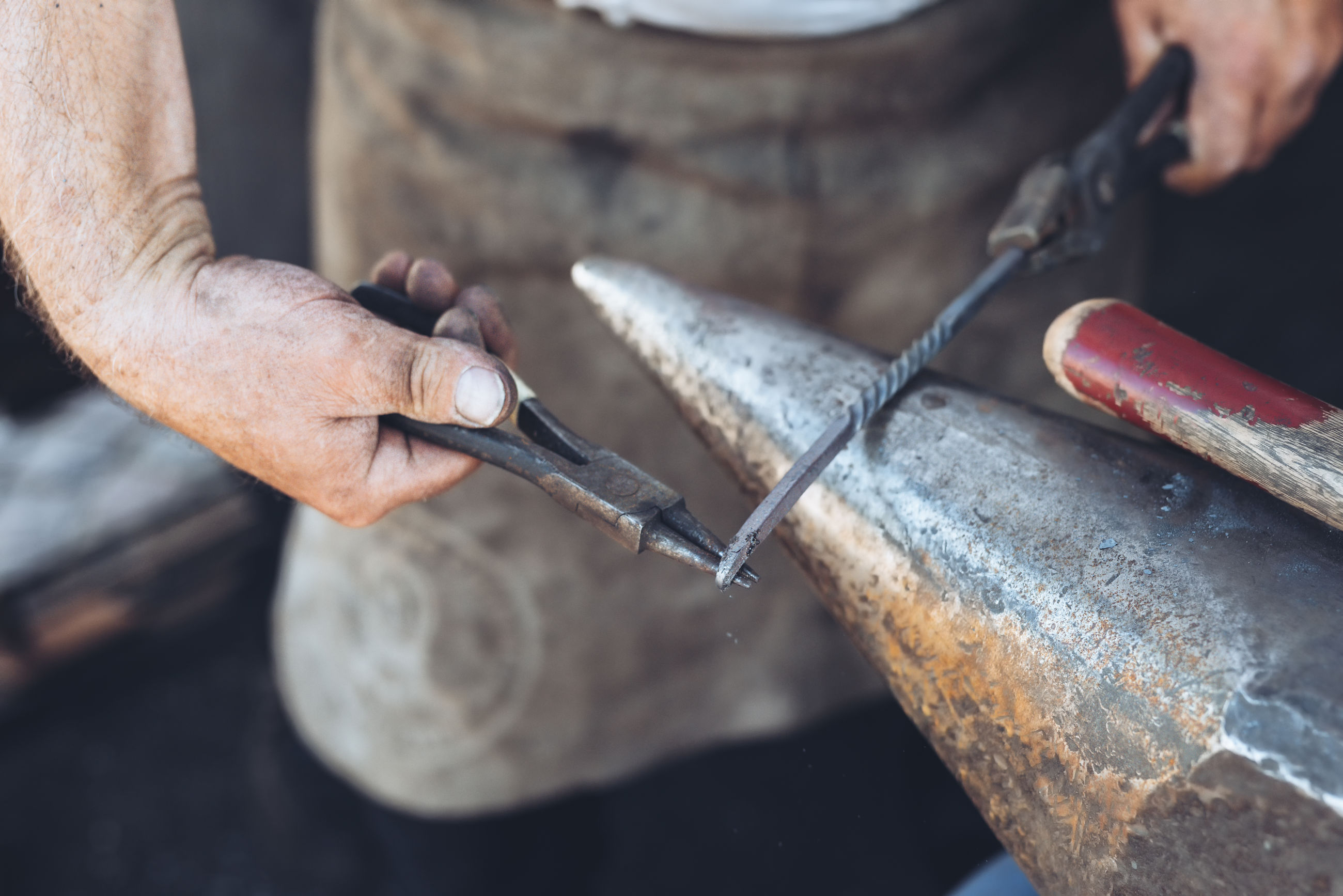 Midsection of man working on metal at workshop