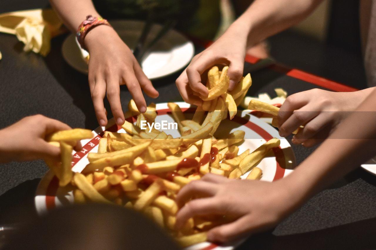Children grabbing french fries