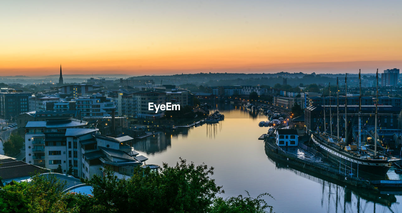 building exterior, architecture, sunset, sky, built structure, water, city, high angle view, nature, residential district, no people, transportation, building, nautical vessel, orange color, mode of transportation, outdoors, cityscape, reflection