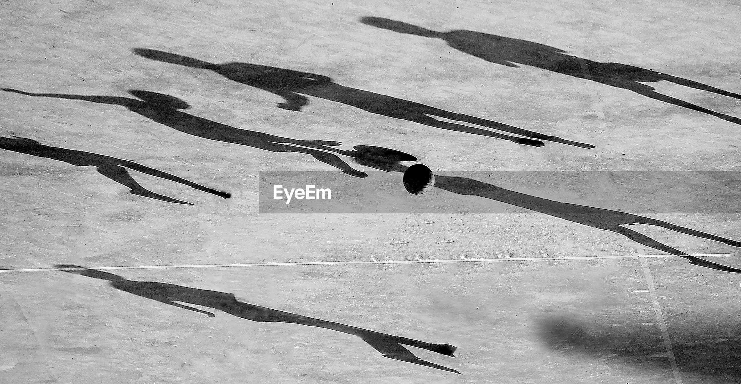 Soccer ball on field with shadows of players