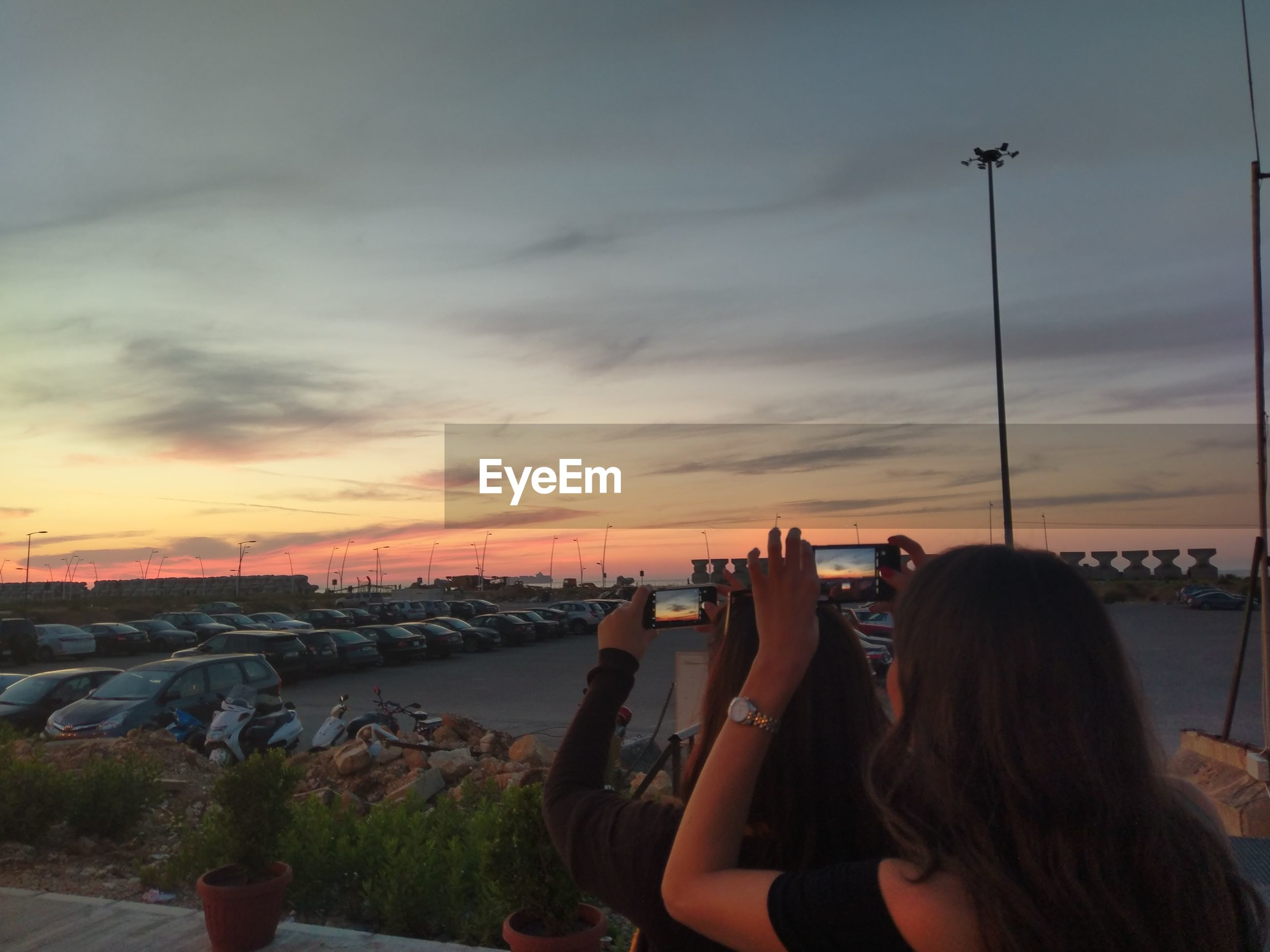 Women photographing sky during sunset