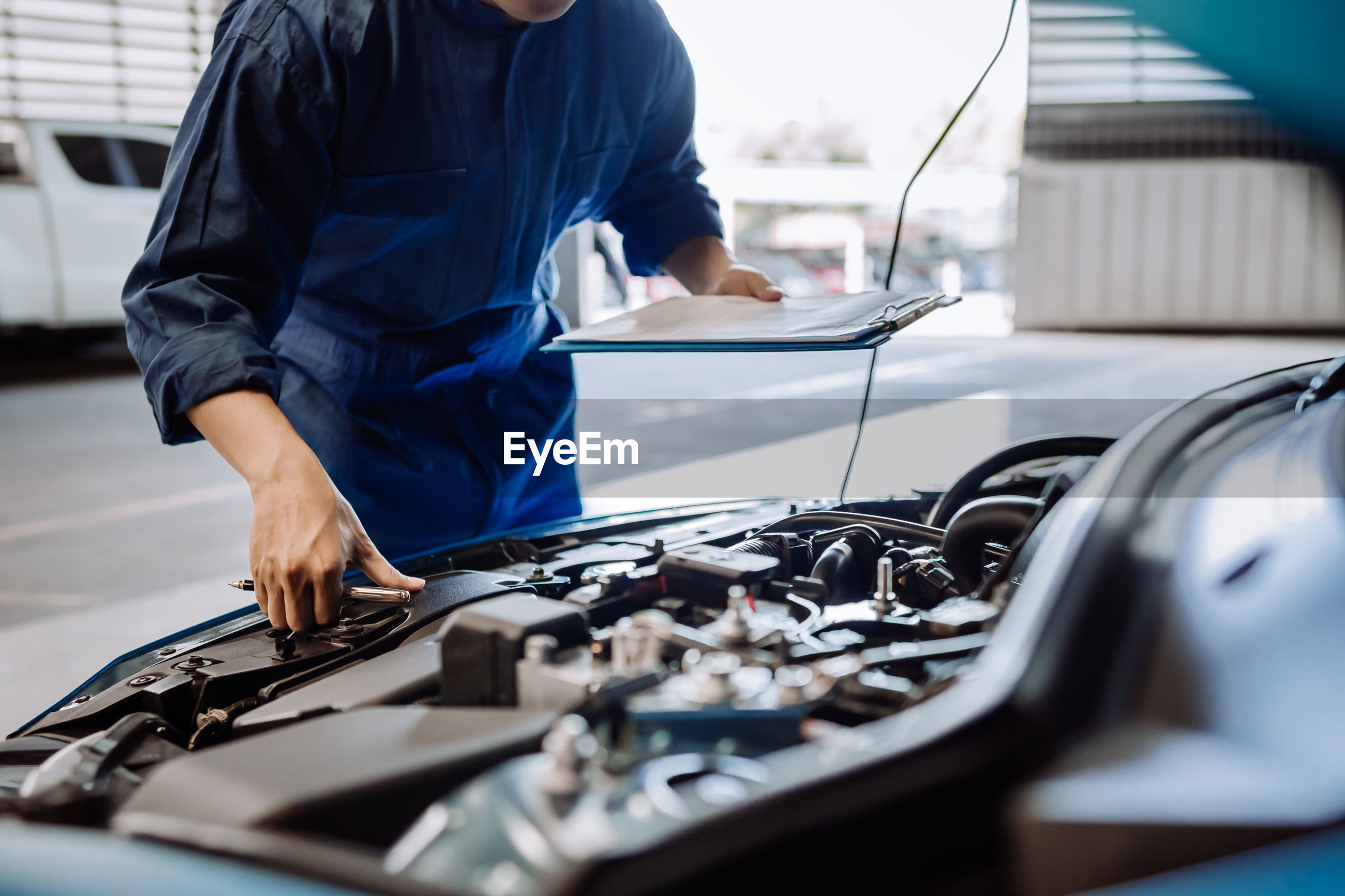 Midsection of mechanic examining car